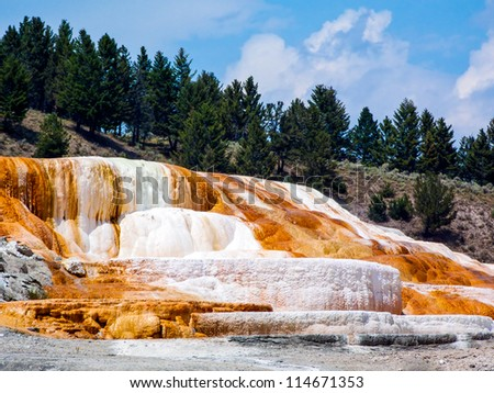 Colorful limestone travertine deposits at mammoth Hot Springs in Wyoming's Yellowstone National Park. - stock photo