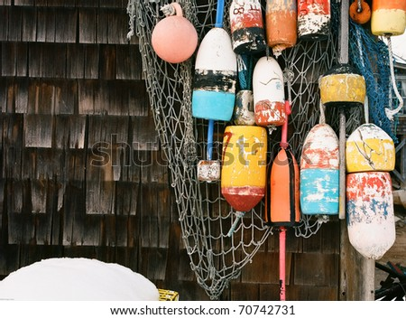 Colorful Lobster buoys and fishing nets hung outside a harbor lobster shack - stock photo