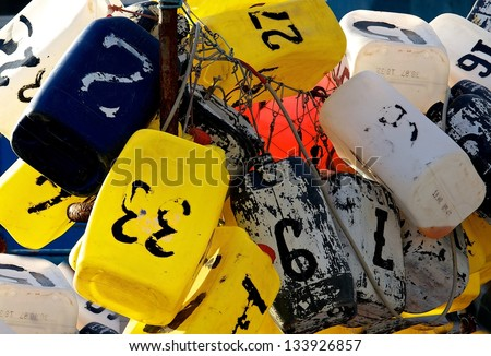 Colorful Lobster Buoys, colorful fishing buoys with numbers, buoys close up,  many buoys in one place fragment view, colorful Lobster buoys for fishing hung outside a harbor - stock photo