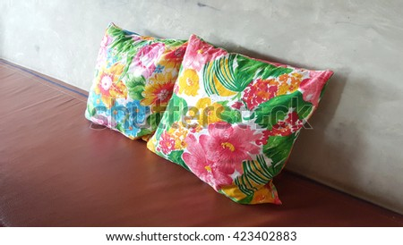 colorful local flower pattern cushion on the bench agaist concrete wall - stock photo
