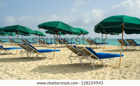 Colorful lounge chairs and umbrellas along the shoreline in beautiful Miami Beach. - stock photo