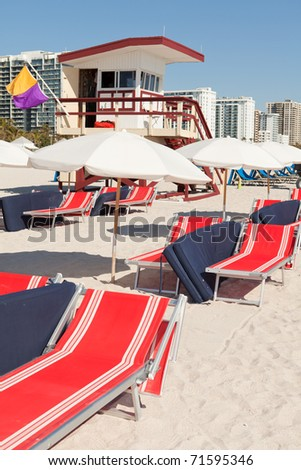 Colorful lounge chairs and umbrellas along the shoreline of South Beach in Miami, Florida. - stock photo