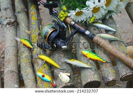 Colorful lures with the fishing rod on the wooden pier - stock photo