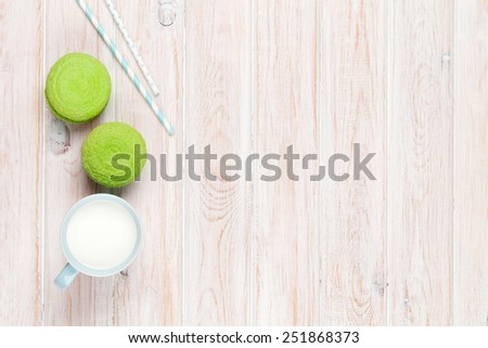 Colorful macarons and cup of milk on white wooden table with copy space - stock photo