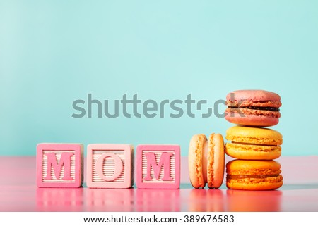 Colorful macarons with mom wood blocks for mothers day on bright pastel background - stock photo