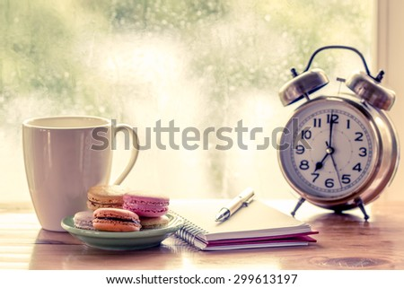 Colorful macaroons and coffee cup with pen on notebook and alarm clock on rainy day window background in vintage color tone - stock photo