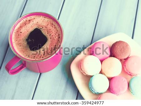 Colorful macrons in a plate and coffee cup over turquoise wood - stock photo
