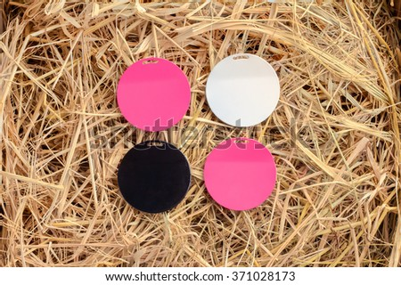 colorful magnet plates on hay background - stock photo