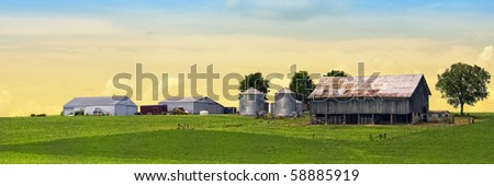 Colorful majestic farm behind green soy field - stock photo