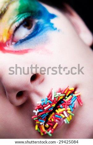 Colorful make-up with candy on her lips - stock photo