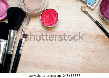 colorful makeup items scattered across a wooden surface - stock photo