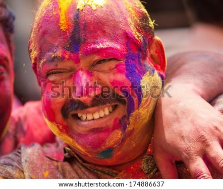 Colorful man face during the Holi celebration on March 27, 2013, Mumbai, Maharashtra, India. Holi is the most celebrated religious color festival in India. - stock photo