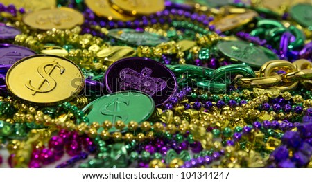 Colorful Mardi Gras beads & coin background - stock photo