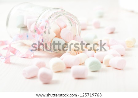 Colorful marshmallows in glass jar with ribbon on light background - stock photo