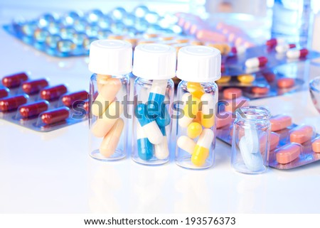 Colorful medical capsules in bottle, on white background. - stock photo