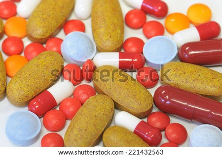 colorful medical therapy with different tablets, pills and capsules - stock photo