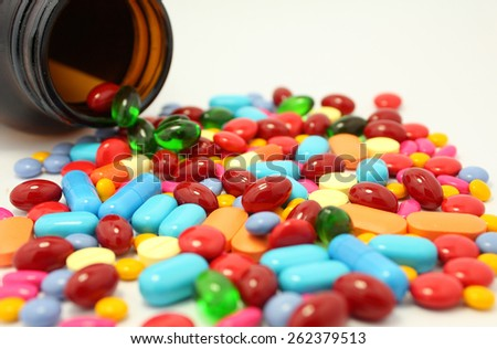 colorful medicine pills and tablets isolated on white with bottle - stock photo