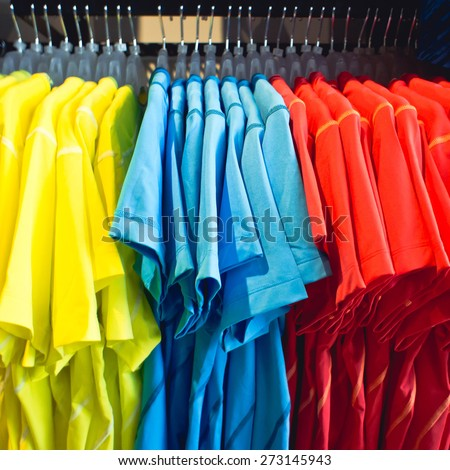 Colorful men's t shirts on a clothing rack - stock photo