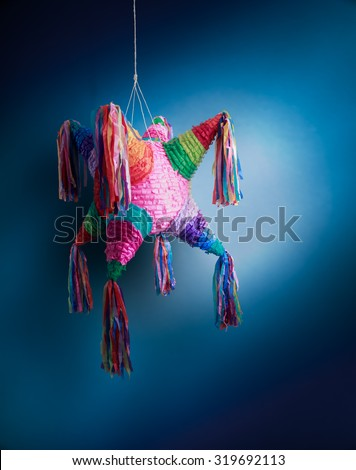 """Colorful mexican """"piñata"""" or pinata used in birthdays on a blue background - stock photo"""