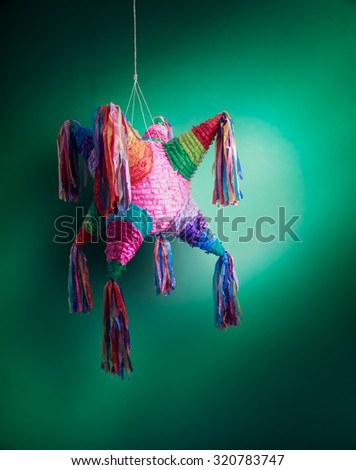 Colorful mexican pinata used in birthdays on green background - stock photo