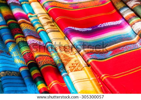 Colorful Mexican serapes hang in row. Woven sarapes - stock photo