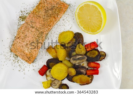Colorful mixed purple, yellow and orange carrot pieces with crimini mushrooms along with poached wild sockeye salmon fillet topped with dill served with a lemon half. - stock photo