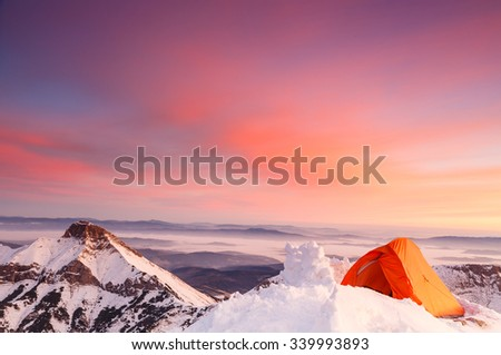 Colorful morning at the top of snow covered mountain with orange tent - stock photo