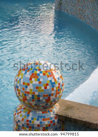 Colorful mosaic  sphere in pool glistening calm pool - stock photo