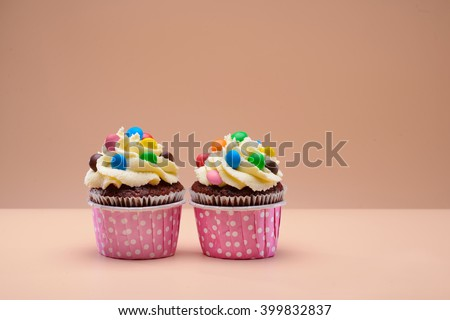 Colorful muffins decorated with round candies on them - stock photo