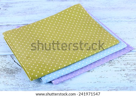 Colorful napkins on wooden table - stock photo