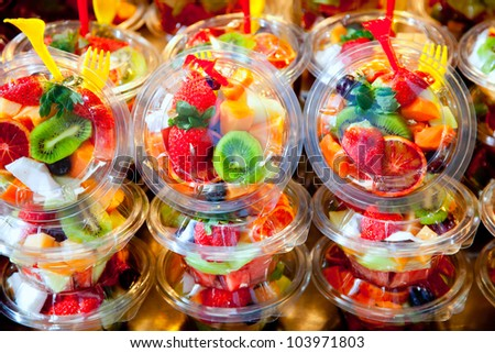 Colorful natural fruit salad transparent glasses in a row - stock photo