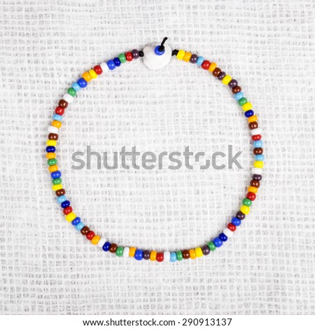 Colorful Necklace Made with Small Plastic Beads Displayed as a Circle - stock photo