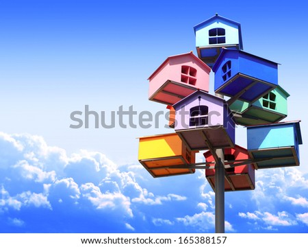 Colorful nesting boxes on blue sky - stock photo