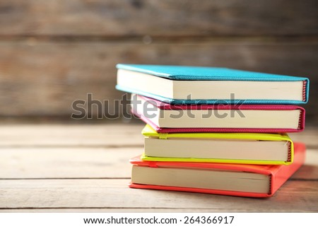 Colorful notebooks on old wooden table - stock photo