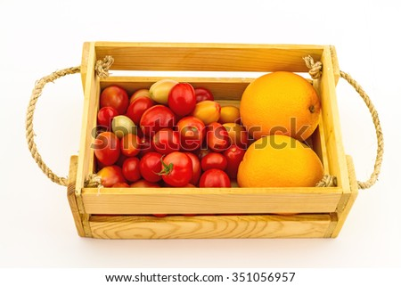 Colorful of fresh tomato and orange  in a wooden box on a white background - stock photo