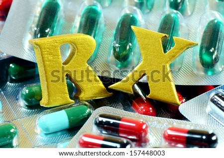 Colorful of oral medications in transparent strips with gold prescription sign. - stock photo