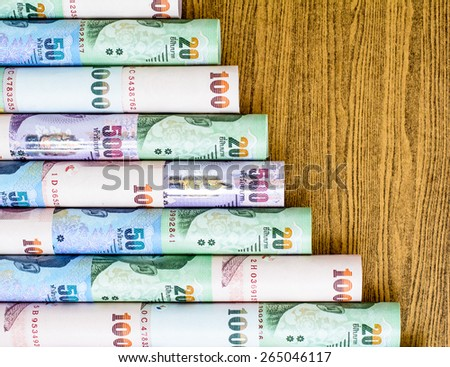 Colorful of Thai currency,banknotes roll put on wooden desk - stock photo
