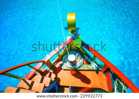 colorful of wood boat against beautiful clear blue sea water with clear water reflection - stock photo