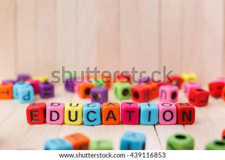 Colorful of word block cube with education text on wooden top table - stock photo