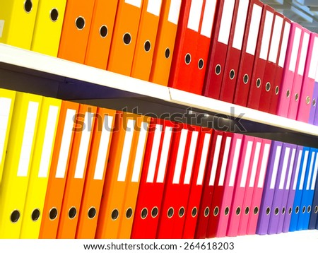 Colorful office folders on the bookshelf - stock photo
