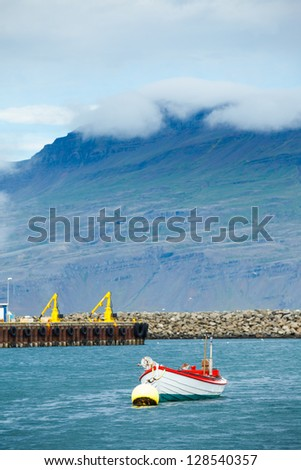 Colorful old boat anchored in the harbor of Husavik Iceland. Vertical view - stock photo