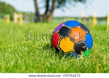 Colorful old football ball on the grass - stock photo