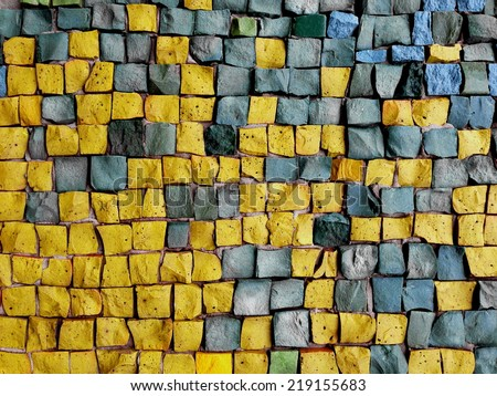 Colorful old stone mosaic on the wall, yellow and grey tiles - stock photo