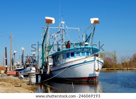 Colorful old wooden shrimp boat trawlers docked along Bayou Lafourche in South Louisiana. - stock photo