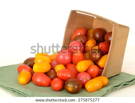 colorful organic cherry tomatoes and bucket on white background - stock photo