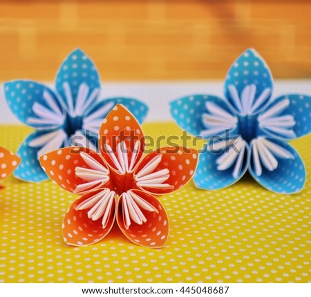Colorful origami flowers made of polka dot paper. Yellow polka dot background. - stock photo