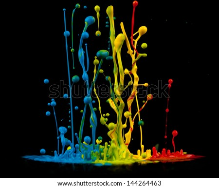 Colorful paint splashing isolated on black - stock photo