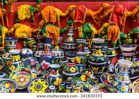 Colorful painted clay vases, pots and toy camels for sale at a street market in India - stock photo