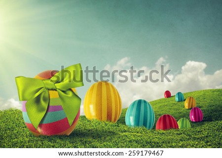 Colorful painted Easter eggs and green bow on a grass field - stock photo