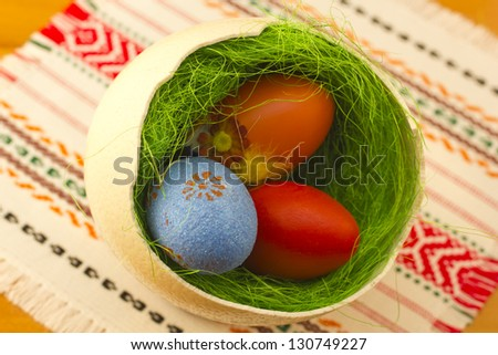 Colorful painted Easter eggs in one big ostrich egg with grass. - stock photo